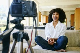 Woman recording video of herself in living room