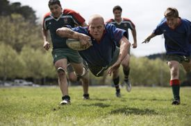 Rugby player scoring jumping on groud with ball