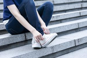 Young woman sitting on steps, tying shoelace