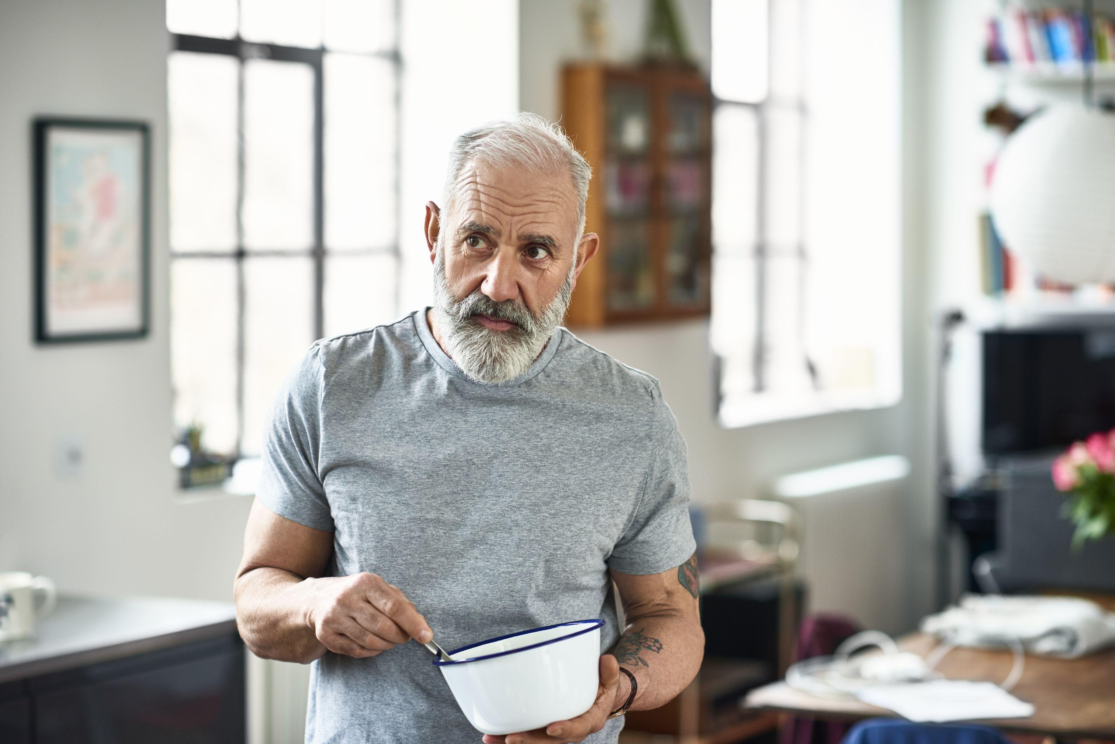 Portrait of senior man holding bowl and preparing food