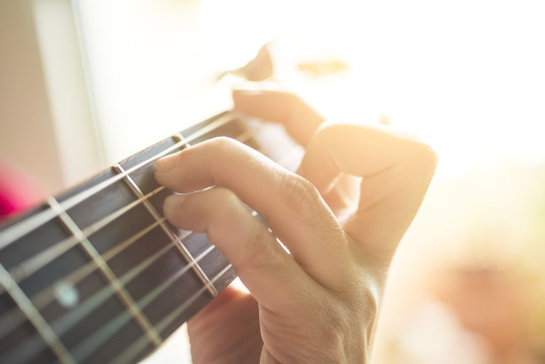 fingers playing on guitar