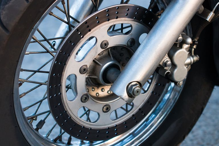 Cropped shot of the shot of the motorcycle forks, tire and front wheel. Disk brake system on a motorcycle. Freedom and travel concept