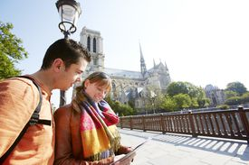 Young couple looking at map at Notre Dame Paris