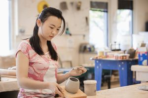 student shaping ceramics in class