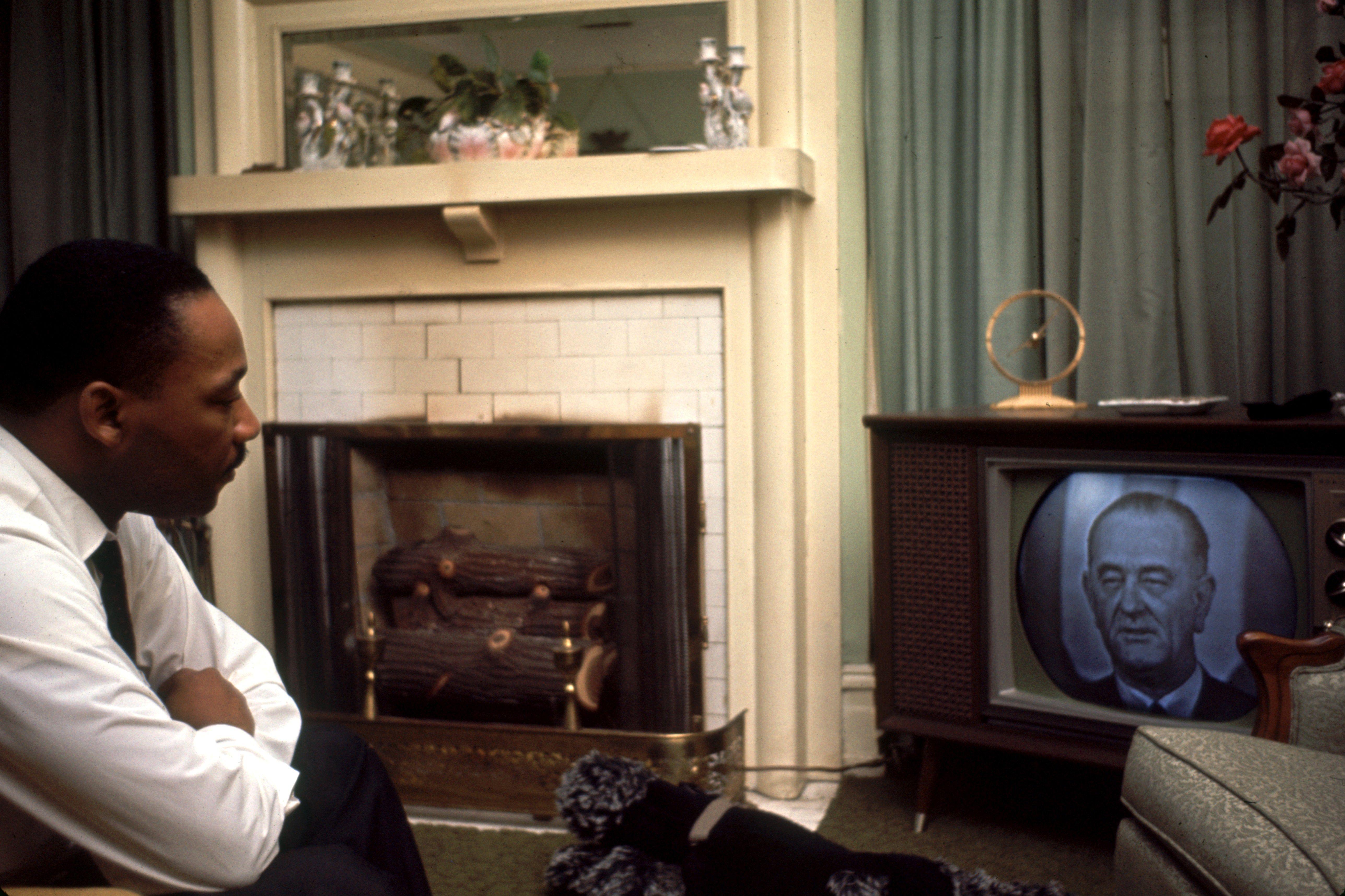 Martin Luther King, Jr. watching President Lyndon Johnson on TV.