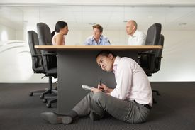 Businessman under desk eavesdropping in office meeting