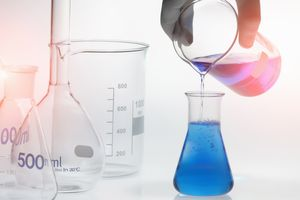 person pouring chemicals from a glass beaker into a glass flask