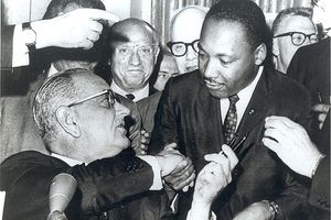 President Lyndon Johnson shakes hands with the Reverend Martin Luther King, Jr., after handing him one of the pens used in signing the Civil Rights Act of July 2, 1964 at the White House in Washington.