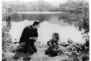 Boris Karloff as the monster sitting lakeside with little girl in a scene from the film 'Frankenstein', 1931.