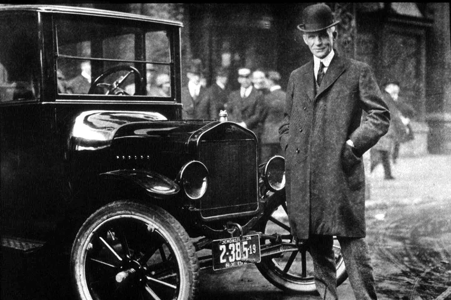 Black and white photo of Henry Ford in front of a Model T.