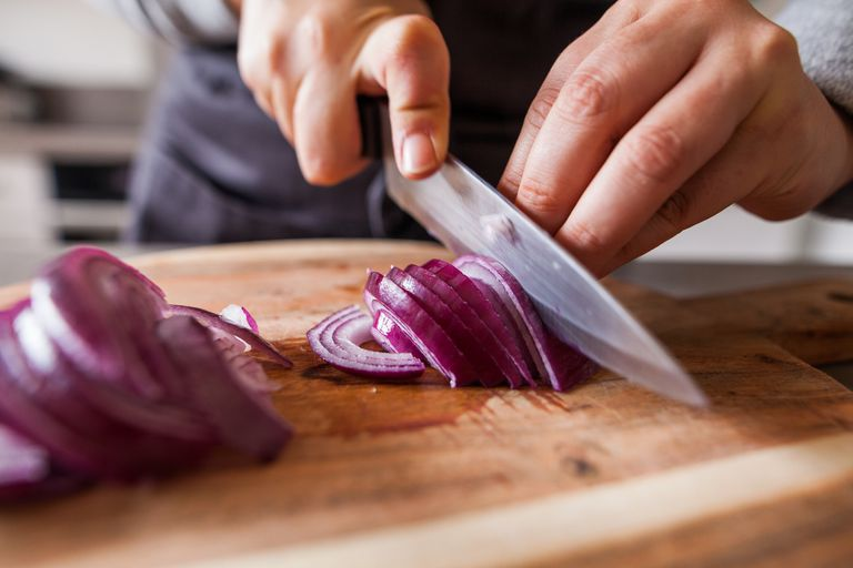 a purple onion being sliced.