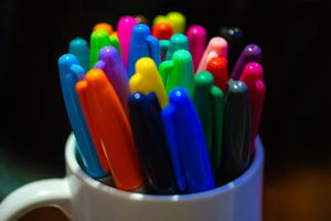 Mug full of Sharpie markers in all different colors.
