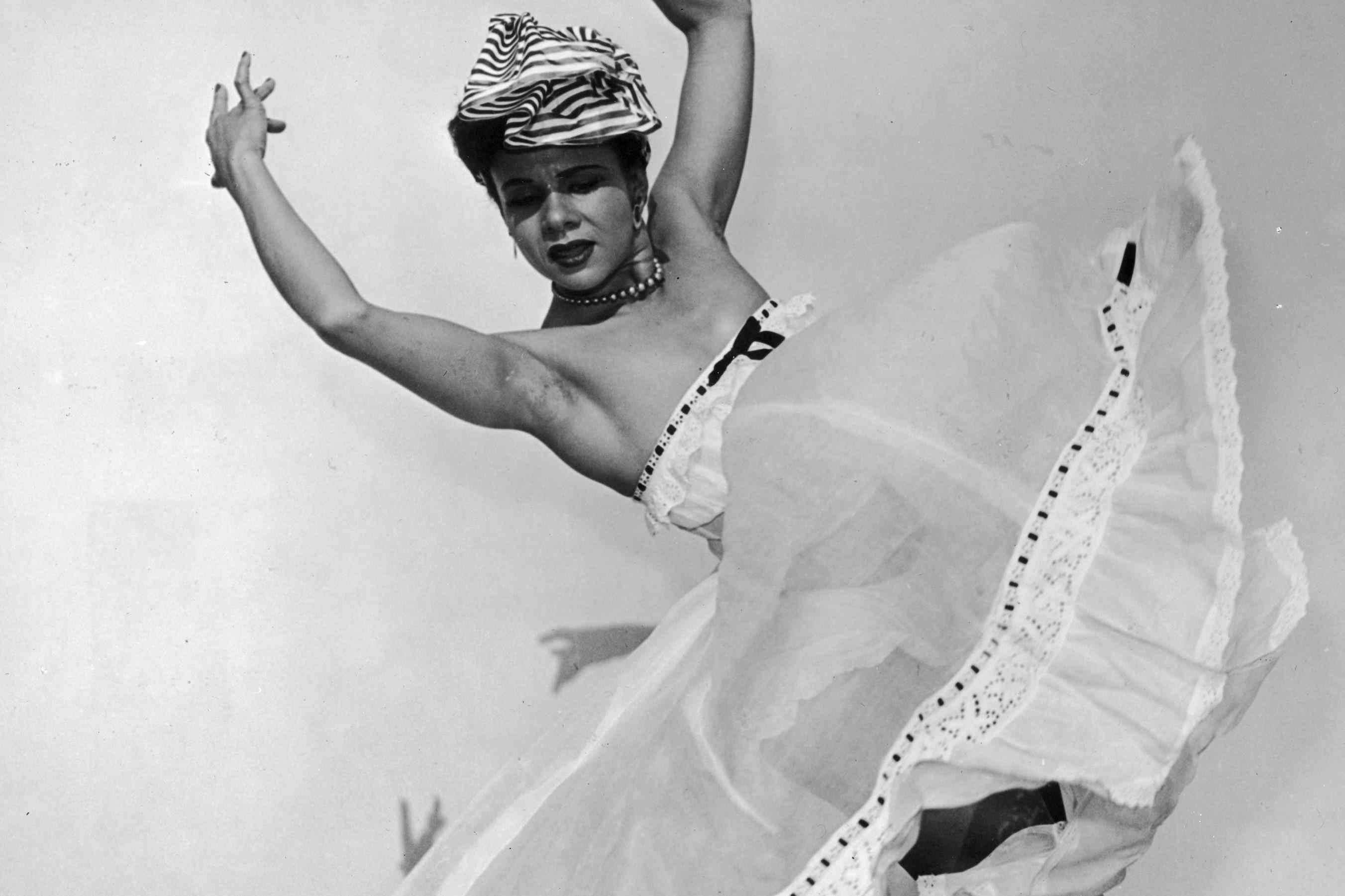 Dancer and choreographer Katherine Dunham wears a striped headdress and flowing skirt and dances with her arms above her head