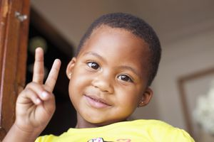 Little girl giving the peace sign.