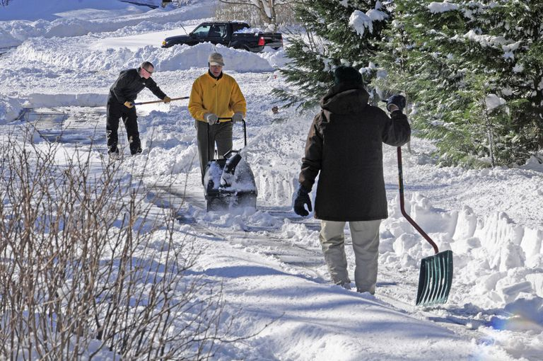 Three people removing snow using a variety of implements.