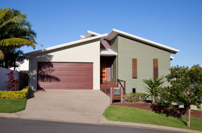 modern stucco home of mossy green with long reddish shuttered windows with sloped roofed two