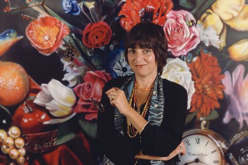 Audrey Flack photographed against a floral painting