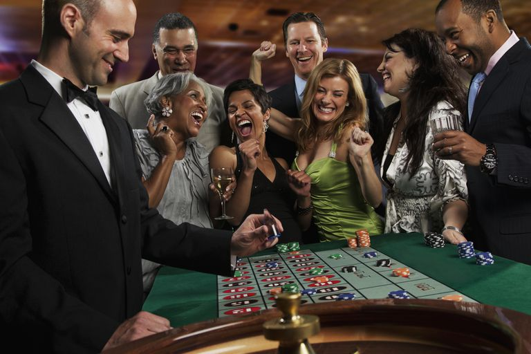 Excited friends gambling at roulette table in casino