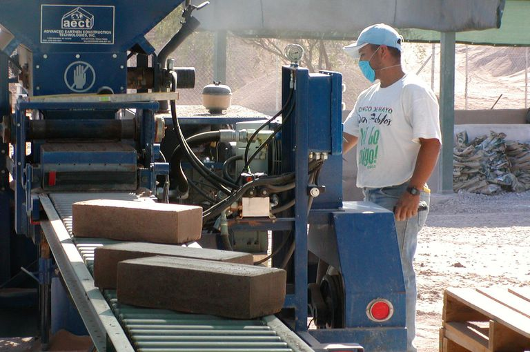 man in t-shirt and dust mask watching blocks roll along conveytor belt