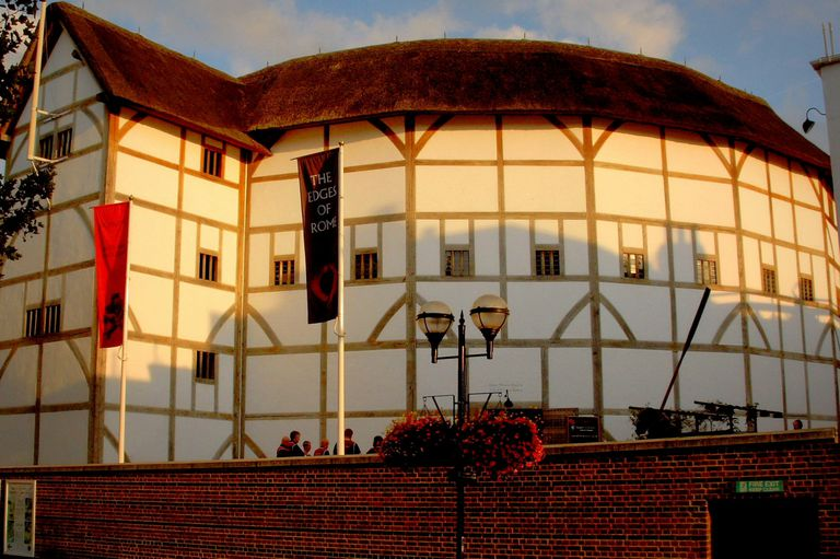 six visible stories of a round, thatched roof building with windows at one upper level and half-timbering siding