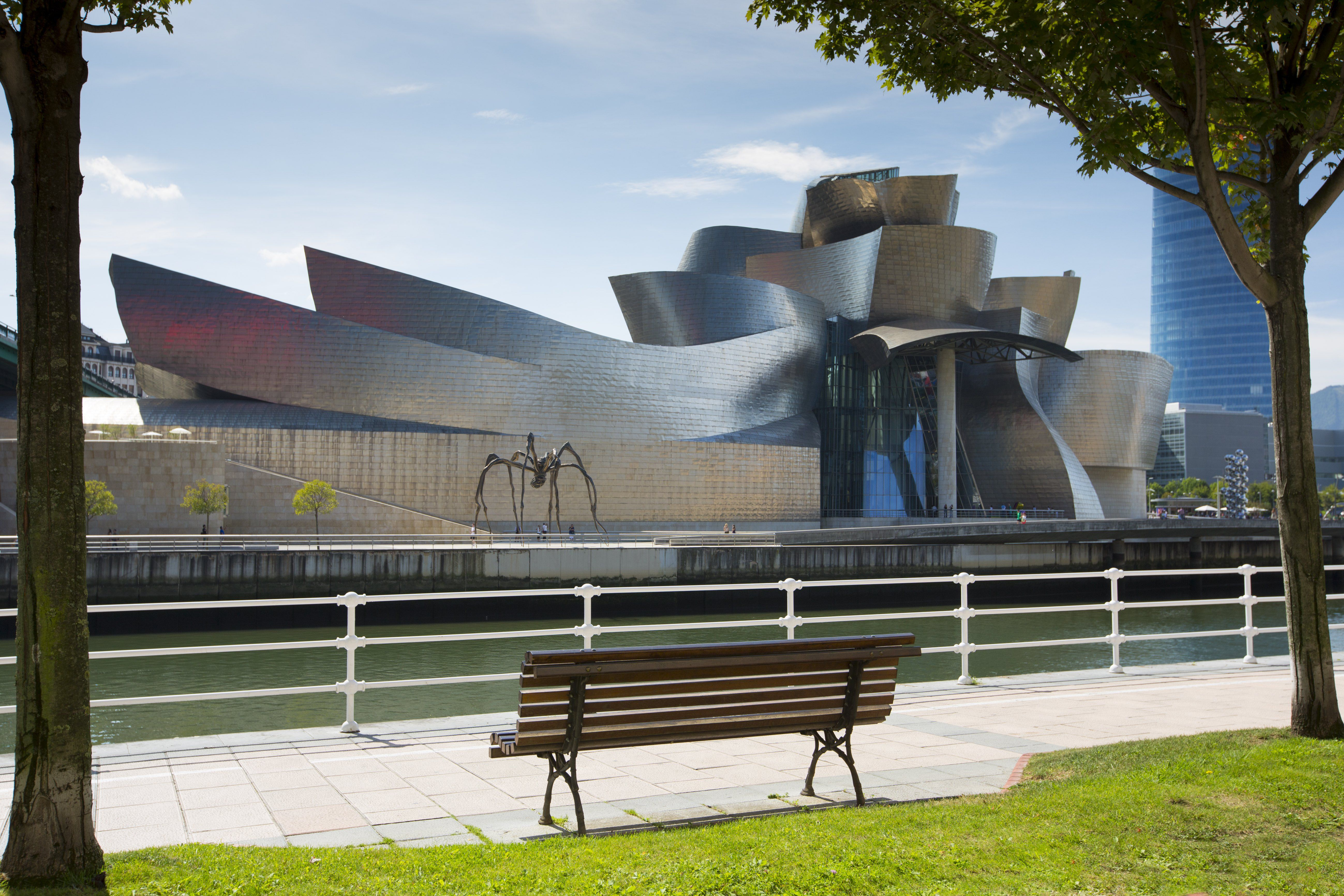 shiny, curvy modern metal building as seen from a park bench across a body of water