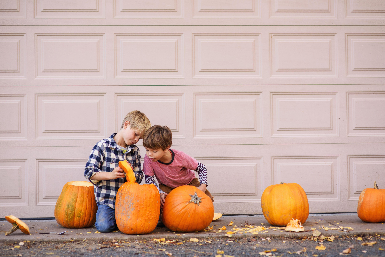 Zwei Jungen sitzen draußen und schnitzen Halloween-Kürbisse