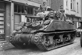Black and white photograph of soldiers riding on a Sherman tank down a street in Germany during WWII.