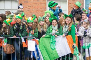 People wearing green celebrating St. Patrick's Day along a parade route.