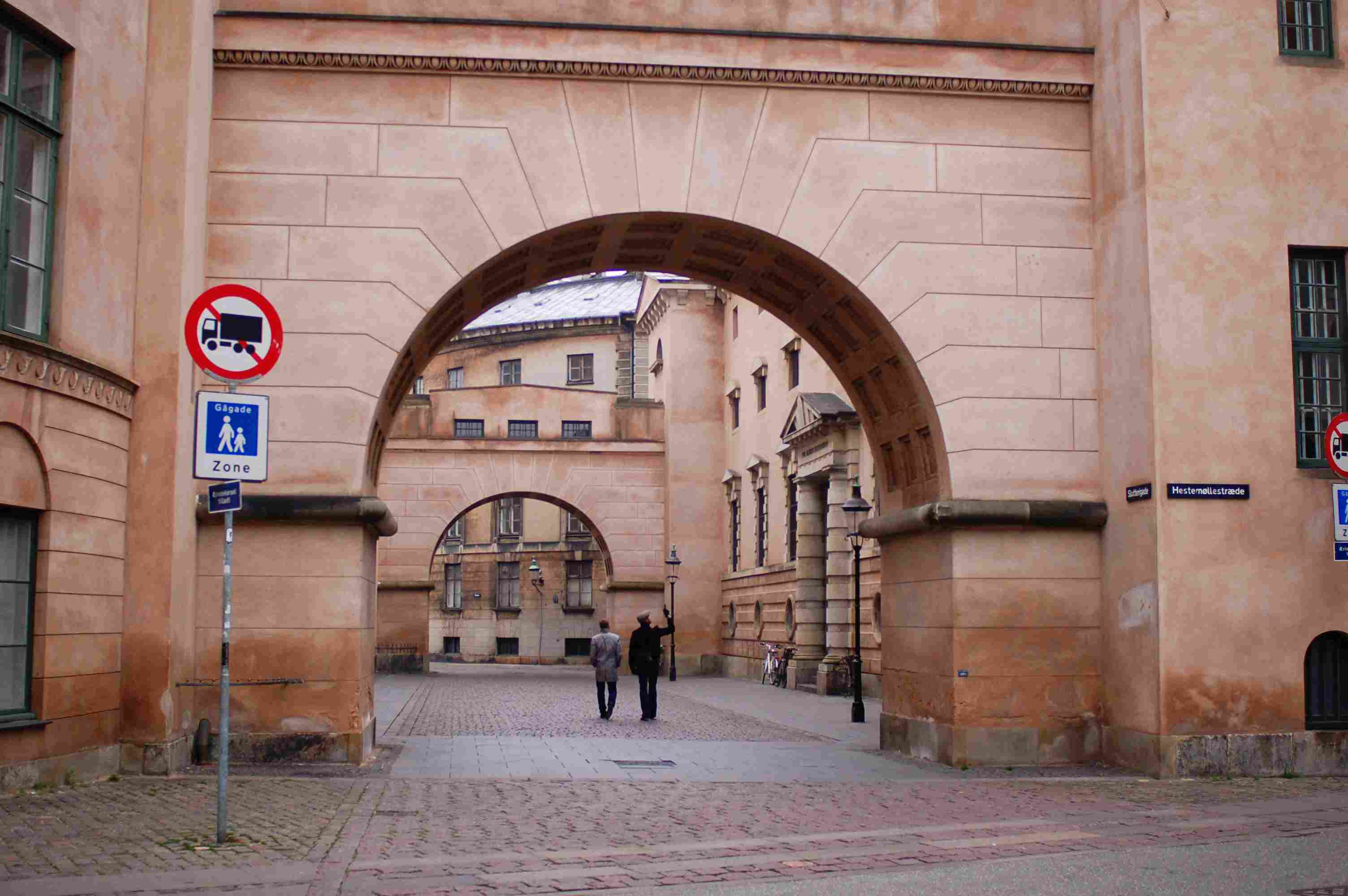 People walking through old archways in Copenhagen