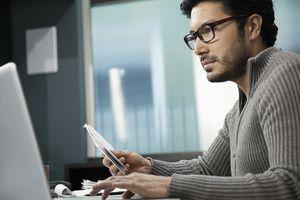 Hispanic man at desk using laptop