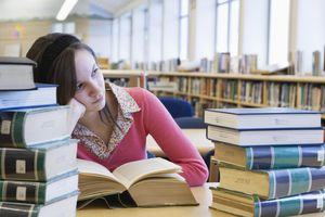 Teenage girl (15-16) sitting with books in library, looking away
