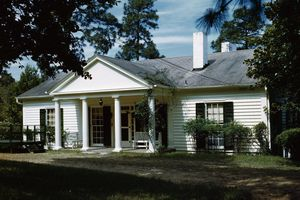 small white house with black shutters, large central portico with four columns and a pediment