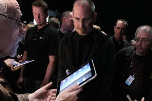 Steve Jobs surrounded by people at an Apple, Inc. event.