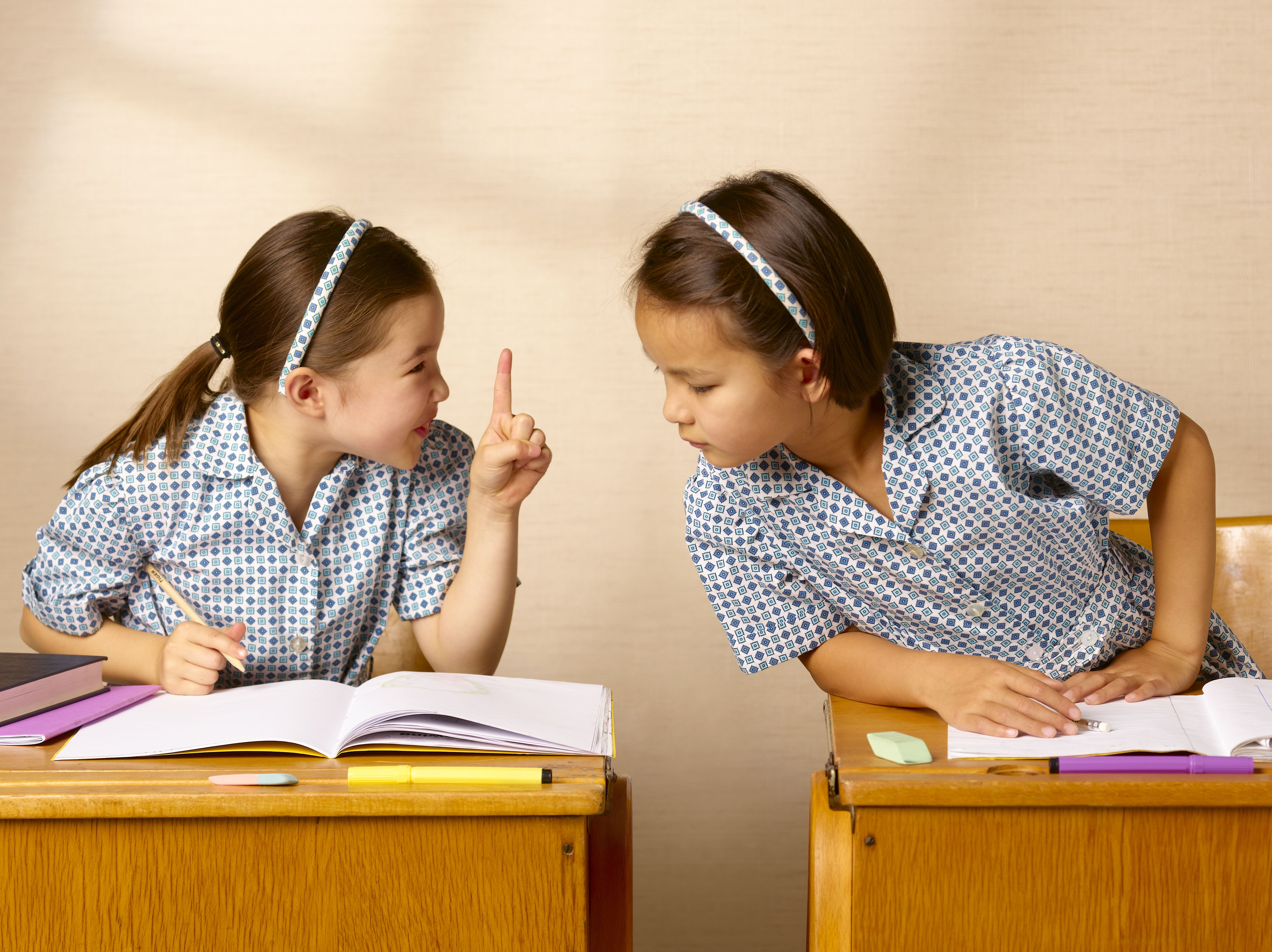 School girl telling neighbor not to cheat/copy