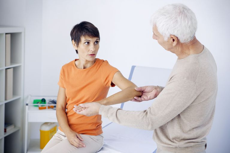Doctor examining patients elbow