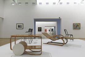 A cart and lounge chairs on display in a large room of a museum
