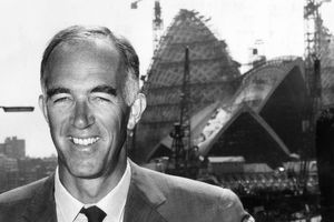 black and white photo of smiling white man in suit in front of a large construction site
