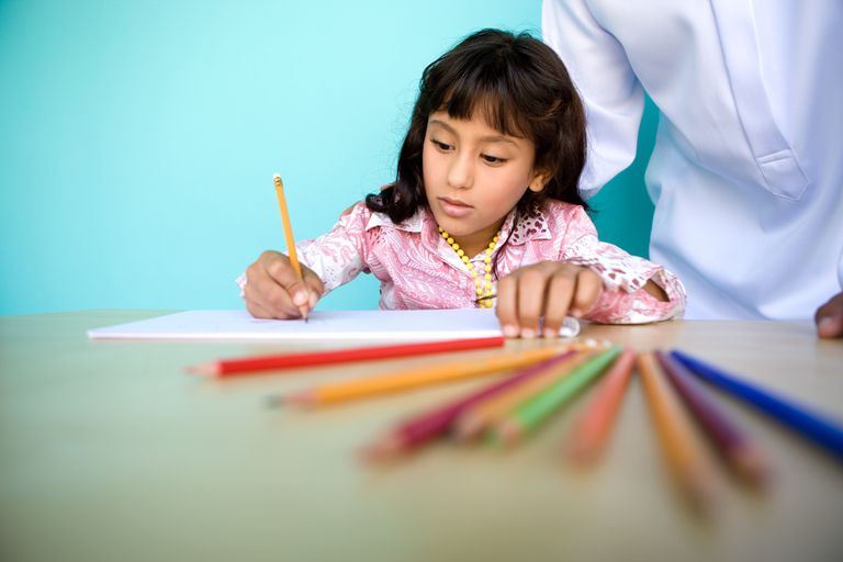 A young girl draws with color pencils.