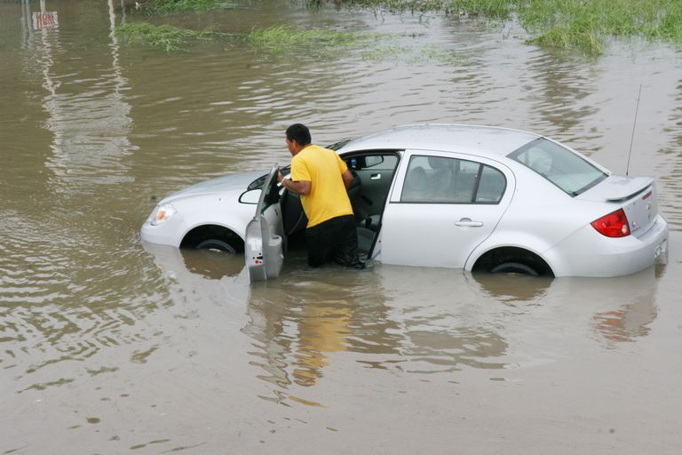 man pushing car in flood