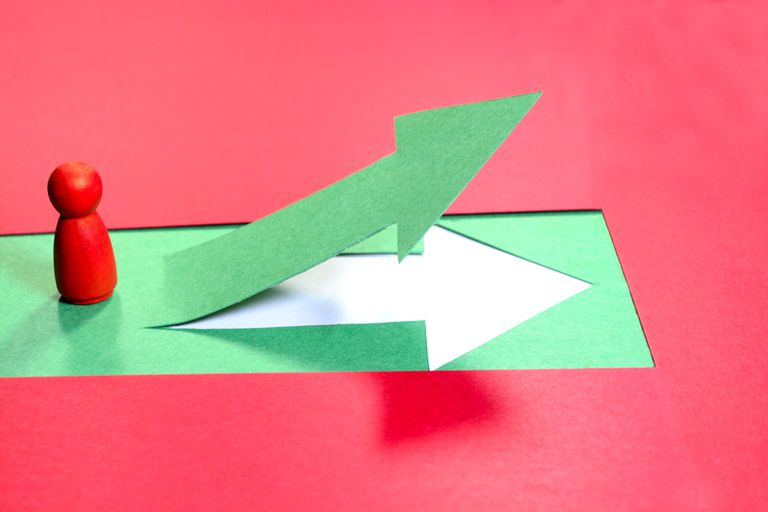 Red wooden figure standing in front of green up arrow. Concept of leadership and success.