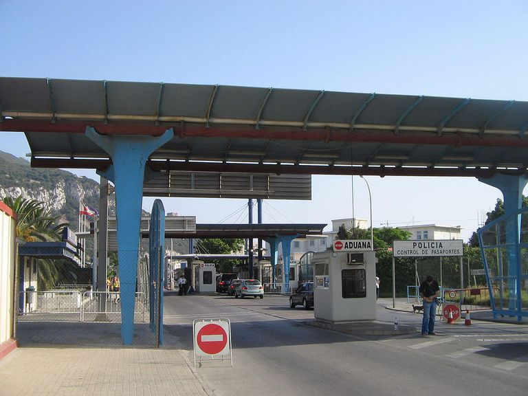 Border crossing with cars and security officials.