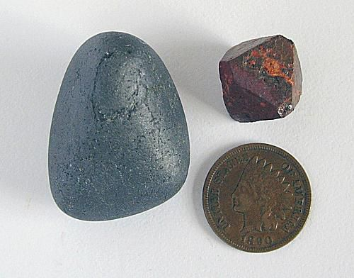Two types of magnetite next to a coin.