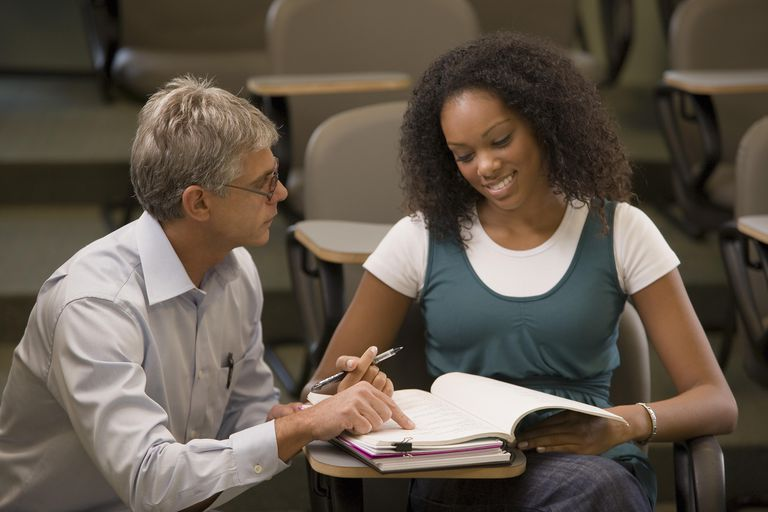 Mature teacher going over work with female student