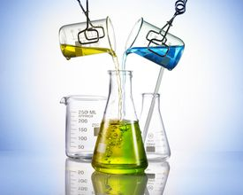 liquids being poured from lab glassware into a beaker