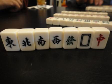 The winds and dragons tiles in a Mahjong set standing upright on a table.