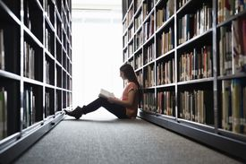 Female student sitting on library floor at college campus