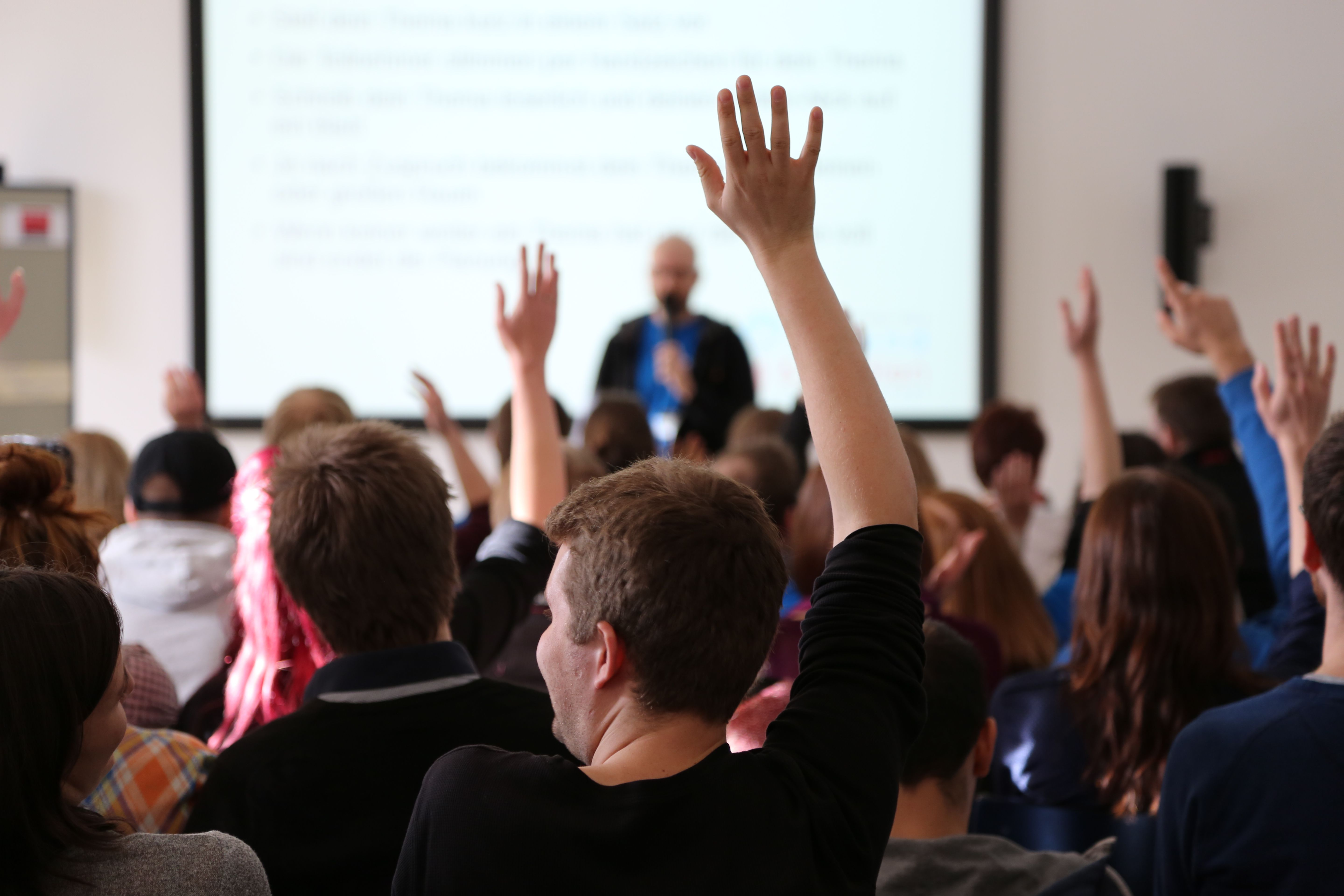 students raising their hands during a lecture