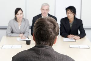 A man being interviewed by three people
