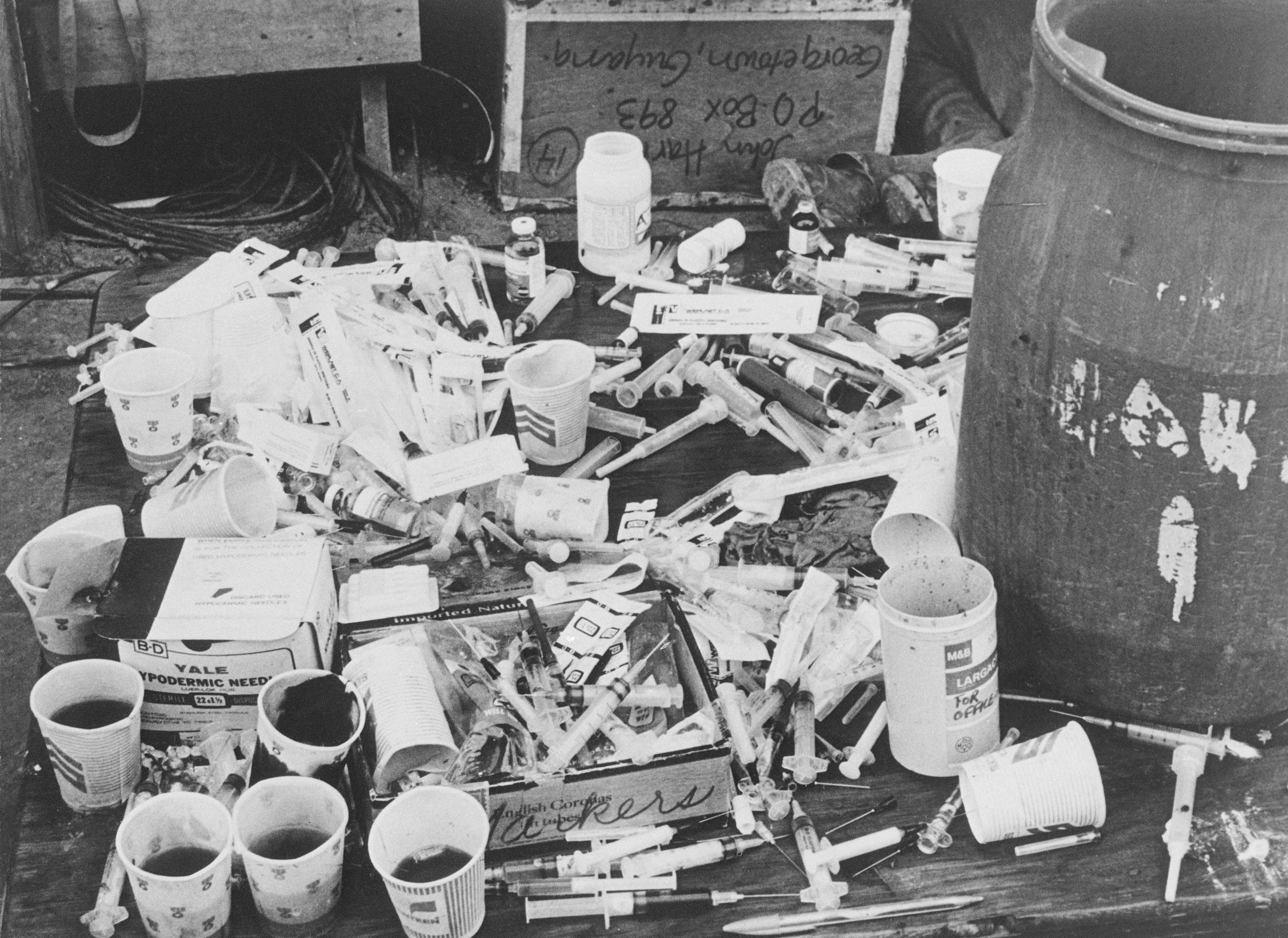 Pile of Syringes and Paper Cups on a table in Jonestown.