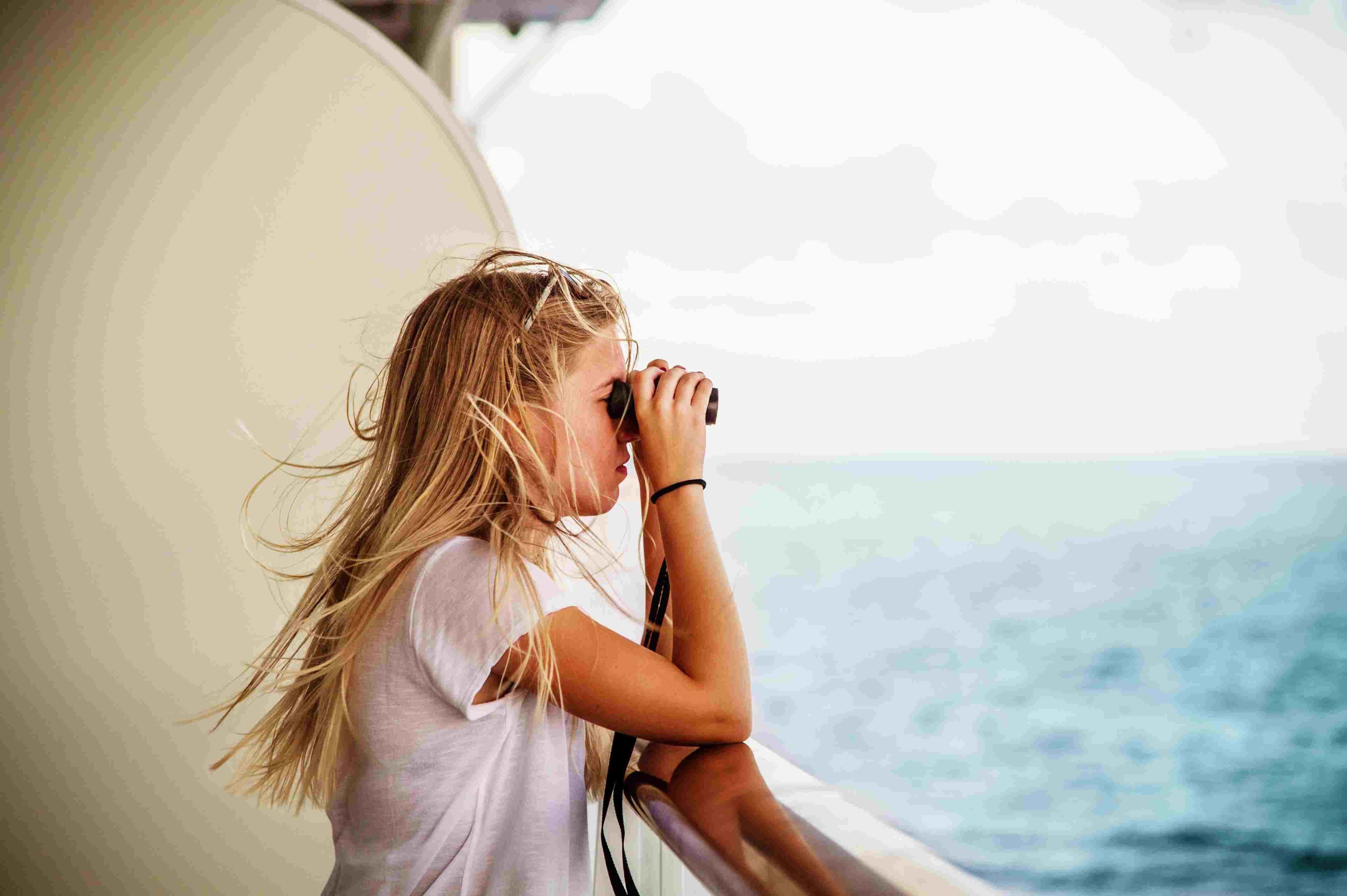 Young woman with binoculars at railing of cruise ship